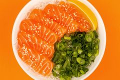 Hawaiian Poke bowl Of Salmon Sashimi With Rice Noodles And Sprin. G Onions Against An Orange Background Stock Photo