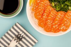 Hawaiian Poke bowl Of Salmon Sashimi With Rice Noodles And Sprin. G Onions Against A Light Blue Background Royalty Free Stock Photos