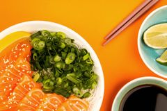 Hawaiian Poke bowl Of Salmon Sashimi With Rice Noodles And Sprin. G Onions Against An Orange Background Royalty Free Stock Images