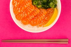 Hawaiian Poke bowl Of Salmon Sashimi With Rice Noodles And Sprin. G Onions Against A Pink Background Royalty Free Stock Photos