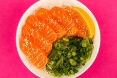 Hawaiian Poke bowl Of Salmon Sashimi With Rice Noodles And Sprin. G Onions Against A Pink Background Royalty Free Stock Photo