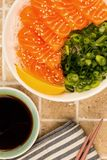 Hawaiian Poke bowl Of Salmon Sashimi With Rice Noodles And Sprin. G Onions On A Tiled Kitchen Table Top Stock Image