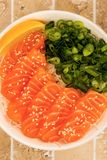 Hawaiian Poke bowl Of Salmon Sashimi With Rice Noodles And Sprin. G Onions On A Tiled Kitchen Table Top Stock Photo
