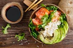 Hawaiian poke coconut bowl with grilled salmon fish, rice and avocado. Healthy food