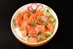 Hawaiian poke with salmon and sesame seeds, boiled rice, fresh c. Ucumber, radish and green onions in porcelain bowl on black background. Top view. Organic royalty free stock photo