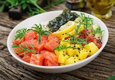 Hawaiian salmon fish poke bowl with rice, avocado, mango, tomato, sesame seeds and seaweeds. Buddha bowl. Diet food Royalty Free Stock Photography