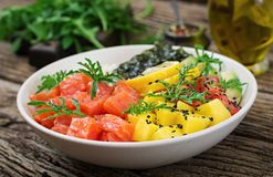 Hawaiian salmon fish poke bowl with rice, avocado, mango, tomato, sesame seeds and seaweeds. Buddha bowl. Diet food Royalty Free Stock Images
