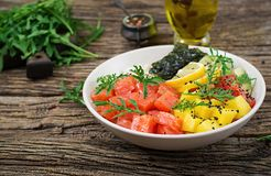 Hawaiian salmon fish poke bowl with rice, avocado, mango, tomato, sesame seeds and seaweeds. Buddha bowl. Diet food royalty free stock photo
