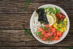 Hawaiian salmon fish poke bowl with rice, avocado, mango, tomato, sesame seeds and seaweeds. Buddha bowl. Diet food. Top view. Flat lay Stock Photo