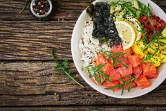 Hawaiian salmon fish poke bowl with rice, avocado, mango, tomato, sesame seeds and seaweeds. Buddha bowl. Diet food. Top view. Flat lay Stock Image