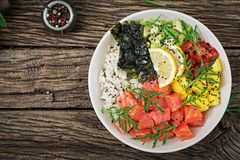 Hawaiian salmon fish poke bowl with rice, avocado, mango, tomato, sesame seeds and seaweeds. Buddha bowl. Diet food. Top view. Flat lay Royalty Free Stock Photos