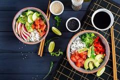 Hawaiian salmon fish poke bowl with rice, avocado, paprika, cucumber, radish, sesame seeds and lime. Buddha bowl. Diet food. Top. View royalty free stock image