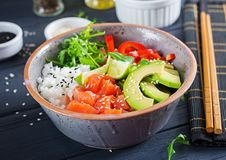Hawaiian salmon fish poke bowl with rice, avocado, paprika, sesame seeds and lime. Buddha bowl. Diet food royalty free stock images