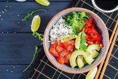 Hawaiian salmon fish poke bowl with rice, avocado, paprika, sesame seeds and lime. Buddha bowl. Diet food. Top view stock photo