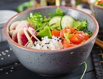 Hawaiian salmon fish poke bowl with rice, cucumber, radish, sesame seeds and lime. Buddha bowl. Diet food royalty free stock photos
