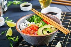 Hawaiian salmon fish poke bowl with rice, cucumber, radish, sesame seeds and lime. Hawaiian salmon fish poke bowl with rice, avocado, paprika, sesame seeds and royalty free stock images