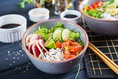 Hawaiian salmon fish poke bowl with rice, cucumber, radish, sesame seeds and lime. Buddha bowl. Diet food stock image