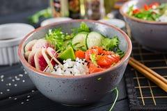 Hawaiian salmon fish poke bowl with rice, cucumber, radish, sesame seeds and lime. Buddha bowl. Diet food stock photography