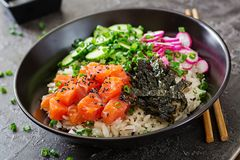 Hawaiian salmon fish poke bowl with rice, radish,cucumber, tomato, sesame seeds and seaweeds. Buddha bowl. Diet food Royalty Free Stock Photos