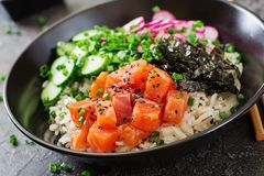 Hawaiian salmon fish poke bowl with rice, radish,cucumber, tomato, sesame seeds and seaweeds. Buddha bowl. Diet food Royalty Free Stock Photography