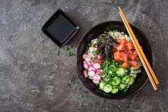 Hawaiian salmon fish poke bowl with rice, radish,cucumber, tomato, sesame seeds and seaweeds. Buddha bowl. Diet food. Top view. Flat lay Stock Images