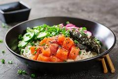 Hawaiian salmon fish poke bowl with rice, radish,cucumber, tomato, sesame seeds and seaweeds. Buddha bowl. Diet food royalty free stock photos