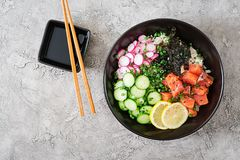 Hawaiian salmon fish poke bowl with rice, radish,cucumber, tomato, sesame seeds and seaweeds. Buddha bowl. Diet food. Top view. Flat lay Stock Photography