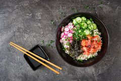 Hawaiian salmon fish poke bowl with rice, radish,cucumber, tomato, sesame seeds and seaweeds. Buddha bowl. Diet food. Top view. Flat lay Royalty Free Stock Photo