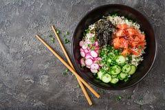 Hawaiian salmon fish poke bowl with rice, radish,cucumber, tomato, sesame seeds and seaweeds. Buddha bowl. Diet food. Top view. Flat lay stock photography