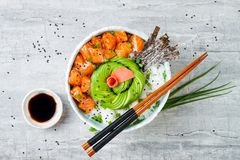 Hawaiian salmon poke bowl with seaweed, avocado rose, sesame seeds and scallions. Top view, overhead, flat lay Stock Photography