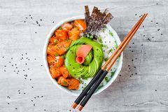 Hawaiian salmon poke bowl with seaweed, avocado rose, sesame seeds and scallions.