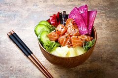 Hawaiian salmon poke bowl with seaweed, watermelon radish, cucumber, pineapple and sesame seeds. Copy space
