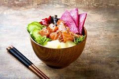 Hawaiian salmon poke bowl with seaweed, watermelon radish, cucumber, pineapple and sesame seeds. Copy space Stock Image