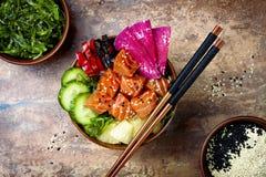 Hawaiian salmon poke bowl with seaweed, watermelon radish, cucumber, pineapple and sesame seeds. Copy space Stock Images