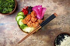 Hawaiian salmon poke bowl with seaweed, watermelon radish, cucumber, pineapple and sesame seeds. Copy space Stock Photo
