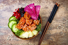 Hawaiian salmon poke bowl with seaweed, watermelon radish, cucumber, pineapple and sesame seeds. Copy space. Background, overhead, flat lay royalty free stock photos