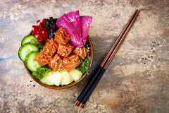 Hawaiian salmon poke bowl with seaweed, watermelon radish, cucumber, pineapple and sesame seeds. Copy space stock images