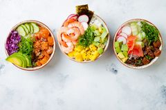 Hawaiian salmon, tuna and shrimp poke bowls with seaweed, avocado, mango, pickled ginger, sesame seeds. Top view, overhead, flat lay, copy space royalty free stock image