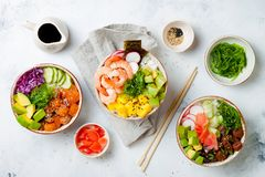 Hawaiian salmon, tuna and shrimp poke bowls with seaweed, avocado, mango, pickled ginger, sesame seeds. stock image
