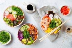Hawaiian salmon, tuna and shrimp poke bowls with seaweed, avocado, mango, pickled ginger, sesame seeds. royalty free stock photo