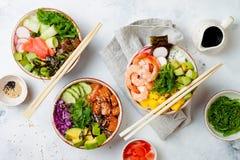 Hawaiian salmon, tuna and shrimp poke bowls with seaweed, avocado, mango, pickled ginger, sesame seeds. Top view, overhead, flat lay stock photos