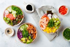 Hawaiian salmon, tuna and shrimp poke bowls with seaweed, avocado, mango, pickled ginger, sesame seeds. stock photos