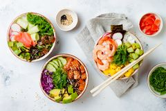 Hawaiian salmon, tuna and shrimp poke bowls with seaweed, avocado, mango, pickled ginger, sesame seeds. royalty free stock photo