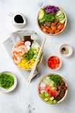 Hawaiian salmon, tuna and shrimp poke bowls with seaweed, avocado, mango, pickled ginger, sesame seeds. royalty free stock image