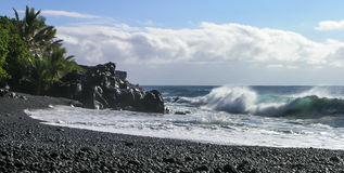 Hawaiian Shores. Waves crash onto a black beach against a cloud filled sky Stock Images