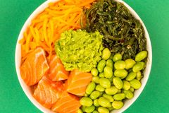 Hawaiian Style Raw Salmon Sashimi Poke Bowl With Edamame Beans A. Nd Seaweed Against A Green Background Royalty Free Stock Photos