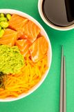 Hawaiian Style Raw Salmon Sashimi Poke Bowl With Edamame Beans A. Nd Seaweed Against A Green Background Stock Photo