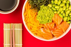 Hawaiian Style Raw Salmon Sashimi Poke Bowl With Edamame Beans A. Nd Seaweed Against A Red Background Stock Photos