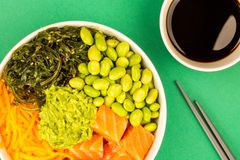 Hawaiian Style Raw Salmon Sashimi Poke Bowl With Edamame Beans A. Nd Seaweed Against A Green Background Royalty Free Stock Photography