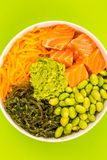 Hawaiian Style Raw Salmon Sashimi Poke Bowl With Edamame Beans A. Nd Seaweed Against A Green Background Royalty Free Stock Image
